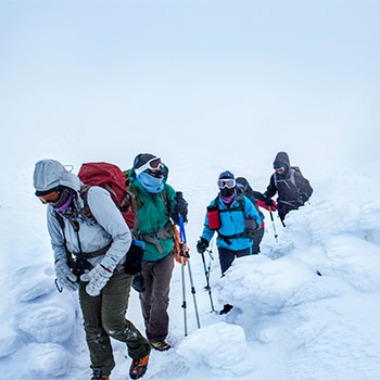 people trudging in snow with trekking poles