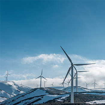 snowy mountains with windmills on top