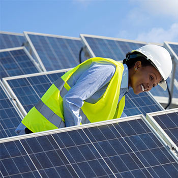 Solar panels being looked at by a smiling black female worker