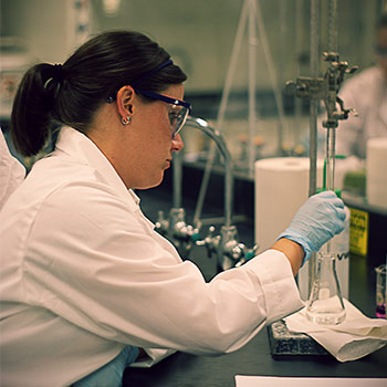 Chemicals being held by a female in a white lab