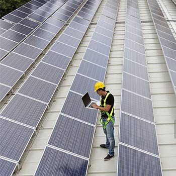 An array of solar panels with a male solar project manager