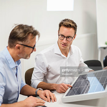 Man being supervised by another man about solar panels