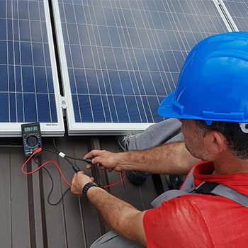 Electricals on a solar panel being tested by a man