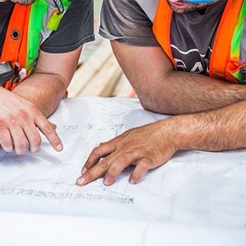 Construction plan under the hands of two men