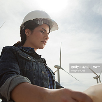 Windmills behind a woman with hard hat