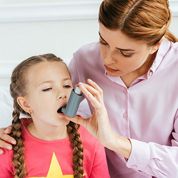 Mother holding an asthma inhaler for her child