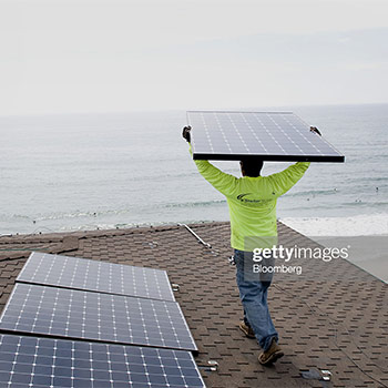 Man wearing a green shirt and holding a solar panel above
