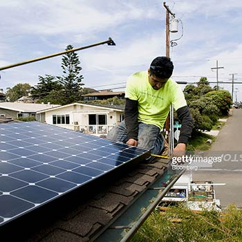 Man on a roof doing solar panel installation