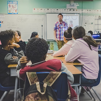A classroom with kids being taught by a man