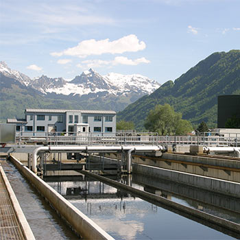 A backdrop of mountains with a wastewater treatment plant in front