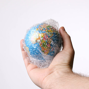 Globe wrapped in plastic packaging being held by a hand