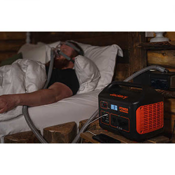 A jackery explorer 1000 power generator beside a man on a bed with a cpap machine