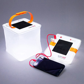 A mobile phone being charged by two inflatable solar lanterns