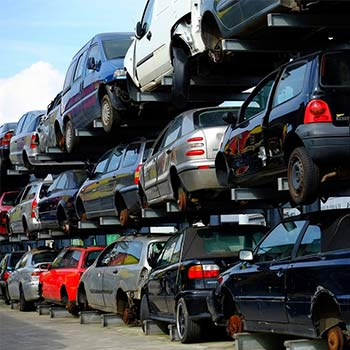 Scrap yard with vehicles stacked on top of each other