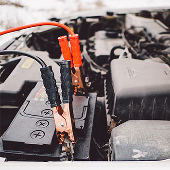 An engine with black and orange jumper cables near it