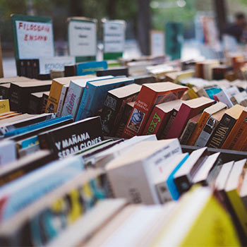 A book sale filled with books stacked beside each other
