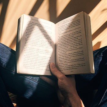 Book held by a hand while being bathed in warm sunlight
